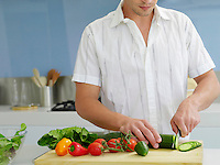Young man cutting vegetables on cutting board in kitchen mid section