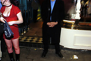 Girl wearing red fish net tights standing next to a security man at a Cardiff city centre bar, Wales, UK, 2002