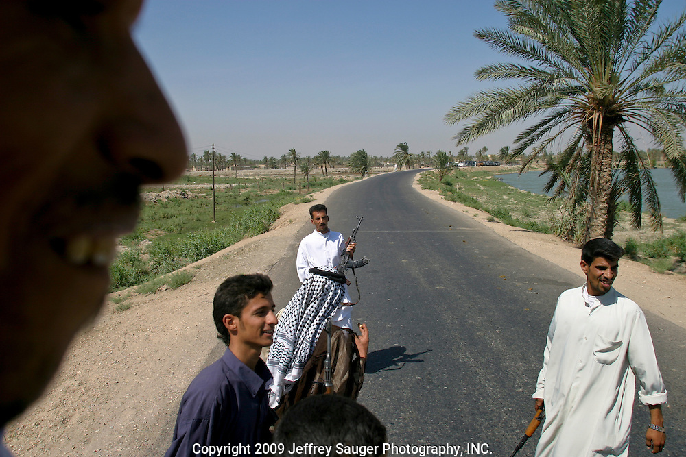 Relatives of the Al-Kasid family ride in a caravan of vehicles on the way to Al-kasid's Istikbal, or homecoming, in his home village Suq ash Shuyukh about 20 miles southeast of Nasiriyah, Iraq, Tuesday, July 29, 2003. Al-kasid is seated at left and the this picture was taken in the village center of Suq ash Shuyukh. The Al-Kasid family fled Iraq after the Gulf War and their part in the uprising against Saddam Hussein in 1991, spent 3 years in Rafa, Saudi Arabia and finally settled in Dearborn, MI. The family hasn't been home to Iraq in 13 years.