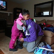 Former Chicago Bear Rashied Davis gets his kids Alanna, 4, (left) and Eli, 2, (not pictured) ready to go play in the snow Friday, Feb. 8, 2013 at home in Mundelein. (Brian Cassella/Chicago Tribune)  B582702588Z.1 <br /> ....OUTSIDE TRIBUNE CO.- NO MAGS,  NO SALES, NO INTERNET, NO TV, CHICAGO OUT, NO DIGITAL MANIPULATION...