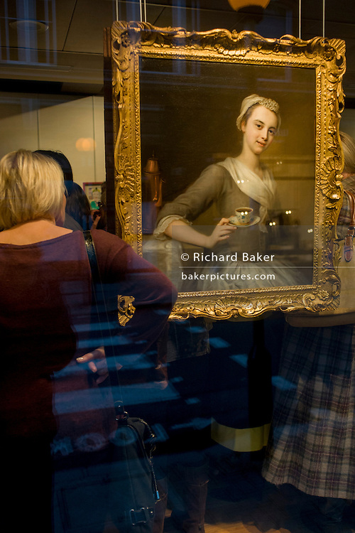 Art lovers are seen through a window while attending a private view of a series at Phillip Mould, a dealer of paintings in London. Philip Mould & Company are a leading specialist dealer in British art and Old Masters. Our gallery is located in Dover Street at the centre of London's art market. We have a large selection of fine paintings for sale, from Tudor and Jacobean panel pictures to eighteenth century landscapes, as well as works by Old Masters such as Titian and Van Dyck, and antique portrait miniatures.