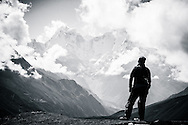 A trekker looks out towards the mountains from the ridge above Machermo, in the Sagarmatha National Park, Nepal.