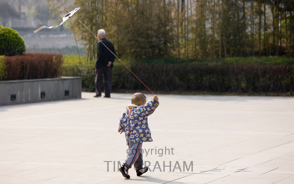 Child playing with a kite in the park by the City Wall, Xian. China has a one child policy to limit population.