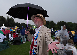 © Licensed to London News Pictures.22/08/15<br /> Castle Howard, North Yorkshire, UK. <br /> <br /> A man checks to see if the rain has stopped following a brief thunderstorm during the 25th anniversary of the Castle Howard Proms event near York. The theme of the event this year is a commemoration of the 75th anniversary of the Battle of Britain and the 70th anniversary of VE day and brings an evening of classic musical favourites celebrating Britishness to the lawns of Castle Howard.<br /> <br /> Photo credit : Ian Forsyth/LNP