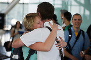 "Honeymooners cuddle in front of other passengers before their round-the-world adventure, leaving from Heathrow Airport's Terminal 5B. The couple are seen embracing at the departure gate as the remaining air travellers filter through the last security checks and board their long-haul flight. The young lady has a look of contentment on her face, the look of happiness and comfort in the arms of her new husband and they hug with all the affection of young love and trust. Another passenger grins in their direction during this show of devotion. From writer Alain de Botton's book project ""A Week at the Airport: A Heathrow Diary"" (2009). ."