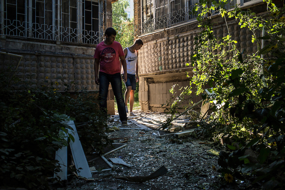Local residents look at damage from a suspected grad rocket strike on an apartment building on Tuesday, July 29, 2014 in Donetsk, Ukraine.