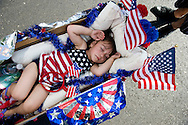 Jalene Torres, 2, figures out a way to grab a nap during the Park Santiago Neighborhood Association's 8th annual Fourth of July parade in Santa Ana Monday July, 4, 2011.