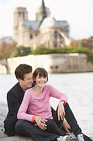 Paris France Couple sitting on river bank in front of Notre Dame Cathedral