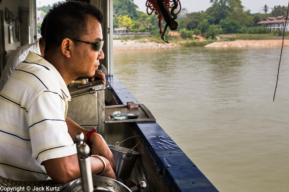 24 APRIL 2014 - CHIANG SAEN, CHIANG RAI, THAILAND:  The captain on a Chinese cargo guides the boat up the Mekong River. The boat was carrying a cargo of cars, Red Bull energy drink and passengers and was bound for Kunming in China. Chinese businesses play an increasingly important role in the Chiang Rai economy. Consumer goods made in China are shipped to Thailand while agricultural products made in Thailand are shipped to China. Large Chinese cargo boats ply the Mekong River as far south as Chiang Saen in the dry season and Chiang Khong when river levels go up in the rainy season.    PHOTO BY JACK KURTZ