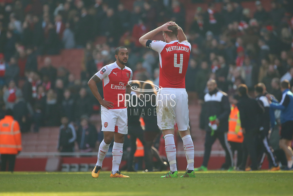 Arsenal defender and captain, Per Mertesacker (4) and Arsenal forward, Theo Walcott (14) after loss during the The FA Cup Quarter Final match between Arsenal and Watford at the Emirates Stadium, London, England on 13 March 2016. Photo by Matthew Redman.