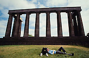 Young couple relaxing at the Greek Temple on top of Calton Hill.