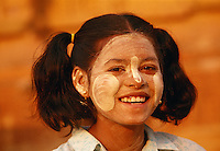 Girl in Bagan with her face covered in thanaka paste to cool and protect her skin.