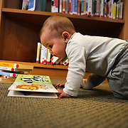 A nine month old baby girl reading library books in a town library. Photo Tim Clayton