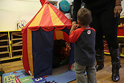 25 October 2013. Manhattan, New York. West Side Family Preschool, 63 W 92nd St. With the help of a teacher, Julius finds his father, who was sleeping in a play tent. 10/25/13. Photograph by Nathan Place/NYCity Photo Wire