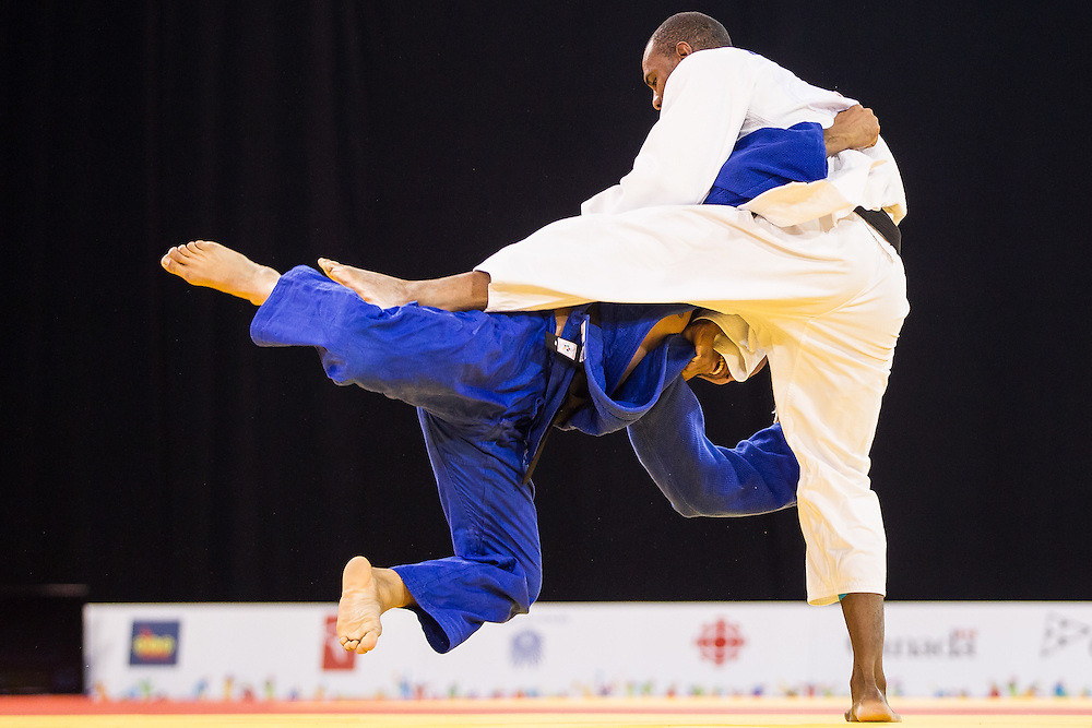 Isao Cardenas (R) of Mexico takes down Nelson Martinez of Venezuela during their men's judo -90 kg 1/4 final at the 2015 Pan American Games in Toronto, Canada, July 13,  2015.  AFP PHOTO/GEOFF ROBINS