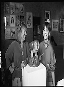 """Pauline Bewick Art Exhibition..1986..03.06.1986..06.03.1986..3rd June 1986..At the Guinness Hop Store,Dublin,artist Pauline Bewick is having an exhibition of her work.The exhibition called """"2 to 50 years""""is a display of her work from age 2 to the present.the art work ranges from simple pencil sketches to more complex paintings and lino cuts...Photograph of the artist,Pauline Bewick, with her daughter Poppy.Poppy helped in the setting up of the exhibition with her mother. In the foreground is the work """"Chianti Owl""""which forms part of exhibition."""