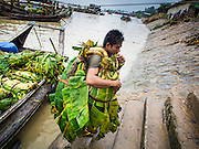 "10 JUNE 2014 - YANGON, MYANMAR:   Porters unload bananas from a river boat at the banana jetty. The ""banana jetty"" is on the Yangon River north of central Yangon on Strand Road. Bananas, coconuts and other fruit are brought in here from upcountry, sold and reshipped to other parts of Myanmar (Burma). All of the labor here is done by hand. Porters carry the produce to the jetty and porters load the boats before they steam upriver.   PHOTO BY JACK KURTZ"