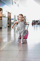Portrait of young adorable little girl running in airport with her pink suitcase