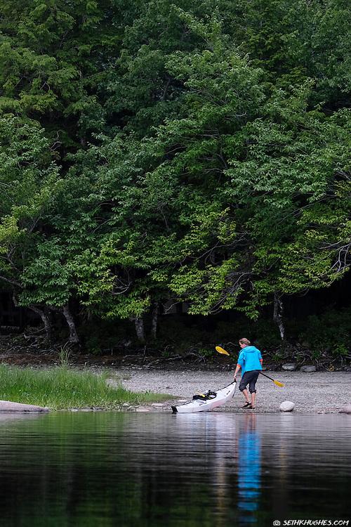 A woman beaches her kayak at Kejimkujik National Park, Nova Scotia, Canada.