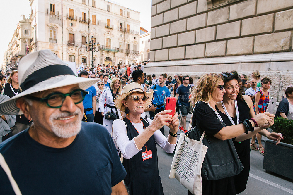 PALERMO, ITALY - 16 JUNE 2018: Visitors attend Marinella Senatore's performance &quot;Palermo Procession&quot; at Manifesta 12, the European nomadic art biennal, in Palermo, Italy, on June 16th 2018.<br /> <br /> Manifesta is the European Nomadic Biennial, held in a different host city every two years. It is a major international art event, attracting visitors from all over the world. Manifesta was founded in Amsterdam in the early 1990s as a European biennial of contemporary art striving to enhance artistic and cultural exchanges after the end of Cold War. In the next decade, Manifesta will focus on evolving from an art exhibition into an interdisciplinary platform for social change, introducing holistic urban research and legacy-oriented programming as the core of its model.<br /> Manifesta is still run by its original founder, Dutch historian Hedwig Fijen, and managed by a permanent team of international specialists.<br /> <br /> The City of Palermo was important for Manifesta&rsquo;s selection board for its representation of two important themes that identify contemporary Europe: migration and climate change and how these issues impact our cities.