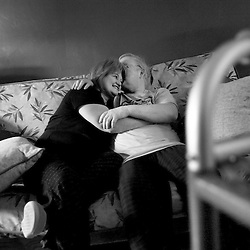 """Sam Bond (right) playfully kisses his wife, Doris (left) during their early morning hours together. Sam is in the secondary progressive stage of multiple sclerosis, but he refuses to take disability. Sam, who can walk only with help of a walker for short distances, is cared for round the clock by his wife, Doris, and son, Jacob. Doris's morning routine is to get Sam out of bed, dressed and bathed, then upstairs to his computer room, where he spends most of the rest of his day. Doris spoke of families who are broken apart by M.S., but said """"How could I leave him (Sam)...He is my best friend...he is my life"""". Sam replied, """"I ask myself sometimes, why am I so blessed? I thank God everyday for my wife and son""""."""