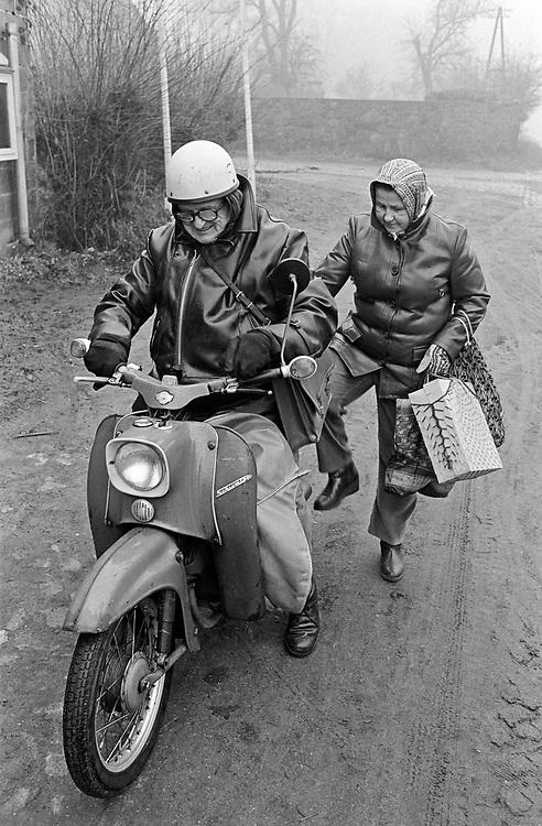 "Germany - DDR - Elderly couple with their Scooter ""Schwalbe"" seen in a village in Eastern Germany - GDR; Älteres Ehepaar mit ihrem Motorroller ""Schwalbe"", gesehen in Beeskow, 03/1990; copyright: Christian Jungeblodt"