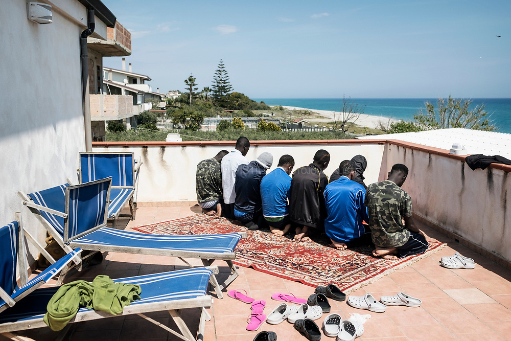 A group of migrants is seen while praying in Riace Marina. (RIACE Apr 2017)