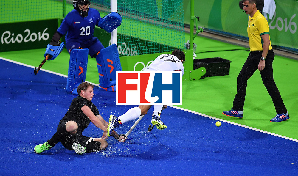 Belgium's Thomas Briels (C) falls and crashes into a referee during the mens's field hockey Belgium vs New Zealand match of the Rio 2016 Olympics Games at the Olympic Hockey Centre in Rio de Janeiro on August, 12 2016. / AFP / MANAN VATSYAYANA        (Photo credit should read MANAN VATSYAYANA/AFP/Getty Images)