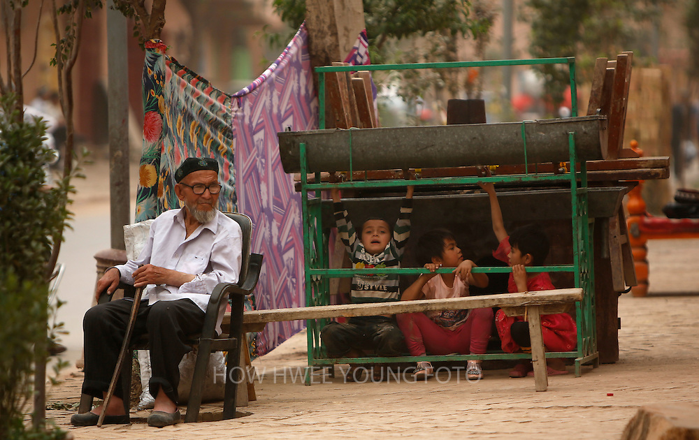 epa03719613 A picture made available on 27 May 2013 of an elderly man of the Uighur ethnic group resting in his chair while children play in a renovated part of the old town of Kashgar, the western edge of China's Xinjiang Uighur Autonomous Region, China 24 May 2013. Kashgar old town's historic labyrinth of earthen mud houses are rapidly being demolished and revamped in a massive government plan to transform the city since 2009. The Chinese government, citing unsafe structures and non-compliance with fire and earthquake safety regulations, has razed and rebuilt more than two thirds of the old city by 2012, relocating thousands of its mainly Uighur ethnic minority residents. Uighurs make up about the majority of the 3.9 million people living in the restive region of Kashgar where the north and south silk road met. Tensions between the Uighurs and Han Chinese have been high as they complain of cultural and religious repression and claim that ethnic Chinese migrants enjoy the main benefits of development in the oil-rich but economically backward region.  EPA/HOW HWEE YOUNG