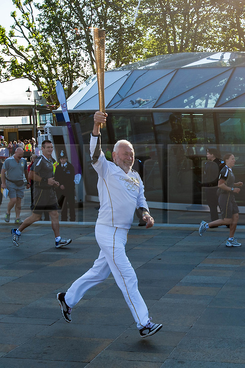 © Licensed to London News Pictures. 21/07/2012. London, UK.  London 2012 Olympics.  Sir Robin Knox-Johnson carries the Olympic Torch around the Cutty Sark ship in Greenwich, London.  Sir Robin was the first person to to sail non-stop around the world, founded the Clipper Round the World Race in 1995, and has been a Cutty Sark Trustee since 2011. Photo credit : Richard Isaac/LNP