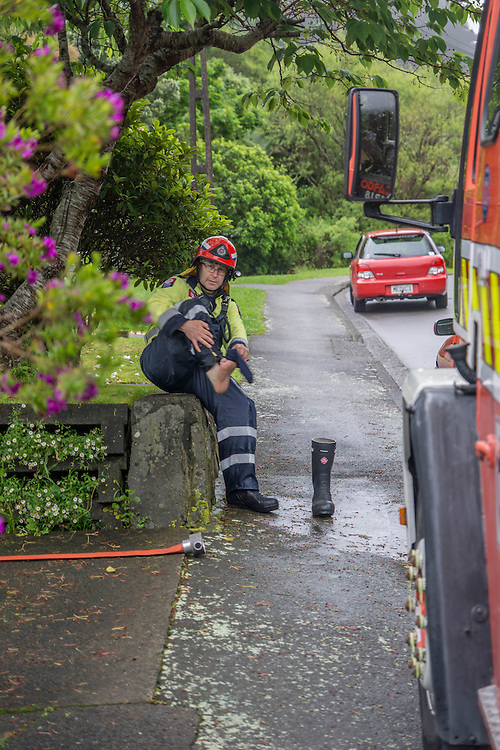 Fireman empties his boot after clearing flooding in Tawa as torrential rains hit the capital, Wellington, New Zealand, Tuesday November 15, 2016. Credit:SNPA / Derek Quinn