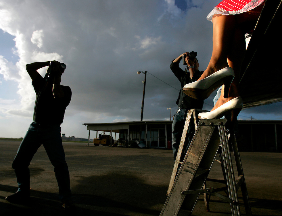 McAllen, TX / 2006 - Rio Grande Valley Calendar Girl Cassandra Keller poses on the wing of a plane for photographers Frank Martinez (right) and Arnold Valdez at McAllen International Airport. Photo by Mike Roy / The Monitor