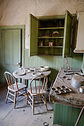 """Dilapidated kitchen with dusty table, counter, and cupboard. Bodie is California's official state gold rush ghost town. Bodie State Historic Park lies in the Bodie Hills east of the Sierra Nevada mountain range in Mono County, near Bridgeport, California, USA. After W. S. Bodey's original gold discovery in 1859, profitable gold ore discoveries in 1876 and 1878 transformed """"Bodie"""" from an isolated mining camp to a Wild West boomtown. By 1879, Bodie had a population of 5000-7000 people with 2000 buildings. At its peak, 65 saloons lined Main Street, which was a mile long. Bodie declined rapidly 1912-1917 and the last mine closed in 1942. Bodie became a National Historic Landmark in 1961 and Bodie State Historic Park in 1962."""