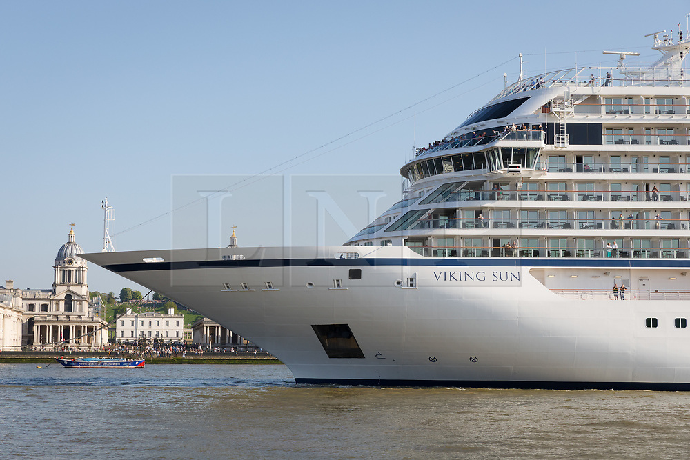 © Licensed to London News Pictures. 06/05/2018. London, UK. People watch as 228-metre-long cruise ship Viking Sun is seen making her way down the River Thames past the Old Royal Naval College at the end of a 3 day visit to Greenwich in south east London. The visit by Viking Sun, which has a capacity of 930 passengers, marks the beginning of London's cruise ship season. For passengers on board, London was the end of a 141 night round the world cruise which started in Miami last December. Photo credit: Vickie Flores/LNP