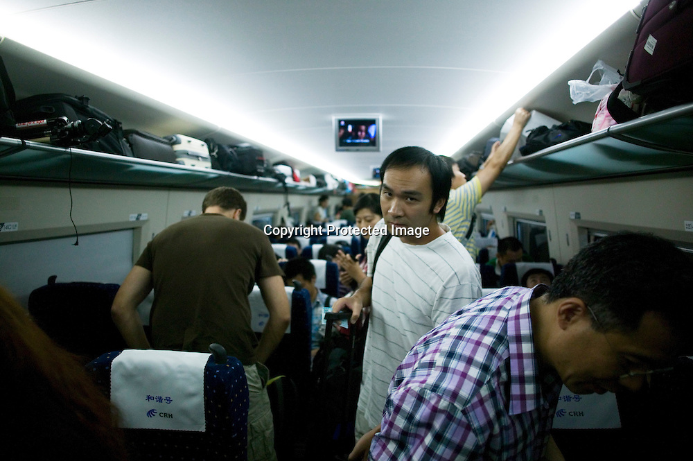 Beijing, September 11 , 2011 : passengers inside the high-speed train after departure for Beijing.the passenger-dedicated trunk line opened in June 2011, reducing the 1,318 km journey between Beijing and Shanghai to less than 5 hours. Trains reach top speeds of 300 km/h (186 mph) for the entire trip.
