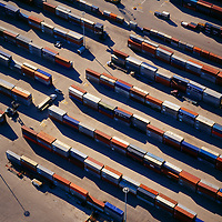 Aerial view of colorful shipping containers waiting to be loaded on board a cargo ship.