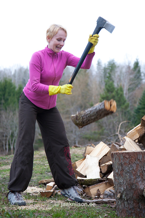 Caucasian Woman Slipping and Chopping Firewood Using Axe