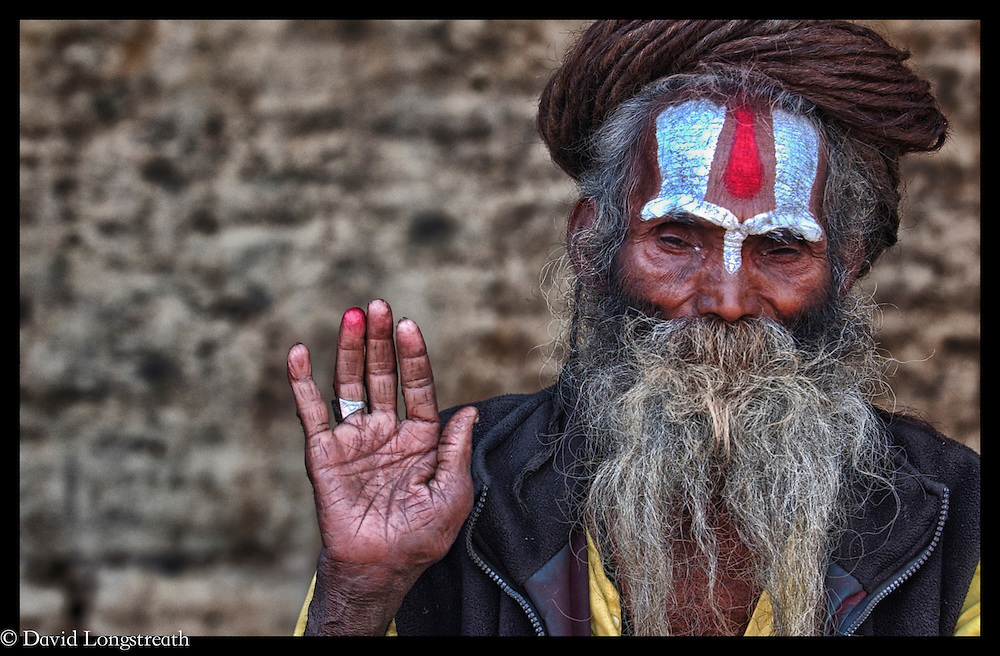 A  Sadhu's look on from a shrine in Katmandu, Nepal.  In Hinduism, sadhu is an ascetic wandering monk.  According to, Wikipdeia,  the sadhu is dedicated to achieving liberation and the final stage of life through meditation and contemplation of brahman.  Sadhus have left behind all material and sexual attachments.  There are 4 to 5 million living in India today.