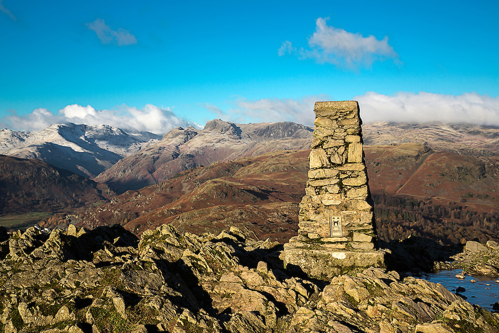 A mountain cairn with  the snow dusted Langdale Pikes in the background