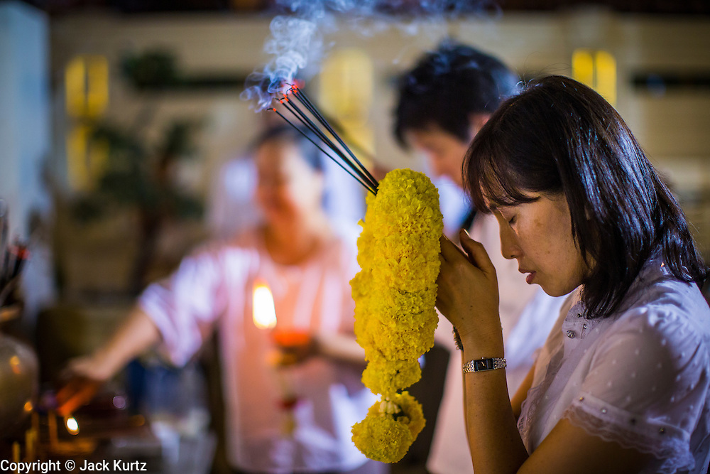 27 JANUARY 2013 - BANGKOK, THAILAND:  A woman prays with incense during Thaipusam at Dhevasathan (the Brahmin Shrines) on Dinso Rd in Bangkok. Thaipusam is a Hindu festival celebrated primarily by the Tamil community in South East Asia on the full moon in the Tamil month of Thai (Jan/Feb). Pusam refers to a star that is at its highest point during the festival. The festival commemorates both the birthday of the Hindu god Murugan, son of Shiva and Parvati, and the occasion when Parvati gave Murugan a vel (a lance) so he could vanquish the evil demon Soorapadman. The holy day is celebrated by Brahmins in Thailand. Brahmanism was the court religion before Buddhism came to Thailand and before the foundation of Sukhothai. Both religions are combined in the Thai way of life and its customs and ceremonies.       PHOTO BY JACK KURTZ