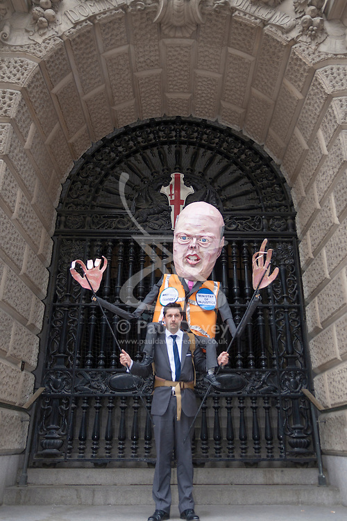 London, June 16th 2014. An effigy of Justice Minister Chris Grayling stands in the entrance of the Old Bailey as lawyers, law students and barristers protest against cuts to legal aid budgets.