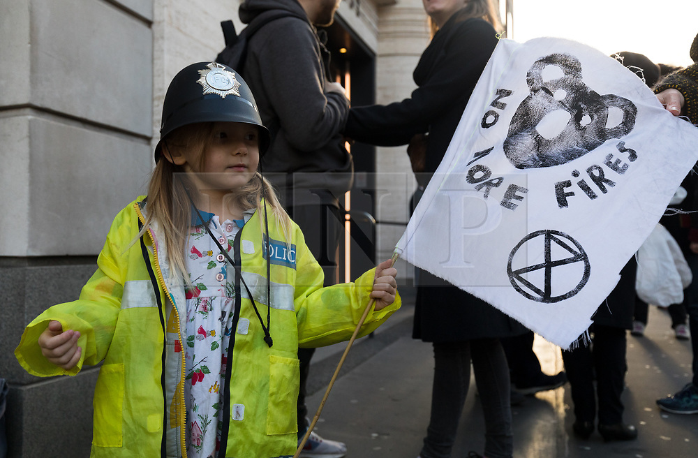 © Licensed to London News Pictures. 16/01/2020. London, UK. A young Extinction Rebellion activist with a police costume and koala banner joins a die in protest outside Siemens London offices, calling for them to pull out of a contract with the new Adani coalmine project in Australia. Environmental activists oppose the mining project and are concerned that the continued use of coal will lead to higher emissions of carbon dioxide, a gas which is linked to global warming.Photo credit: Vickie Flores/LNP