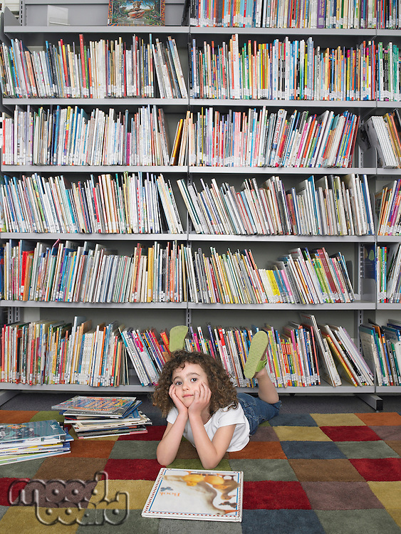 Girl lying on stomach in front of library bookshelf