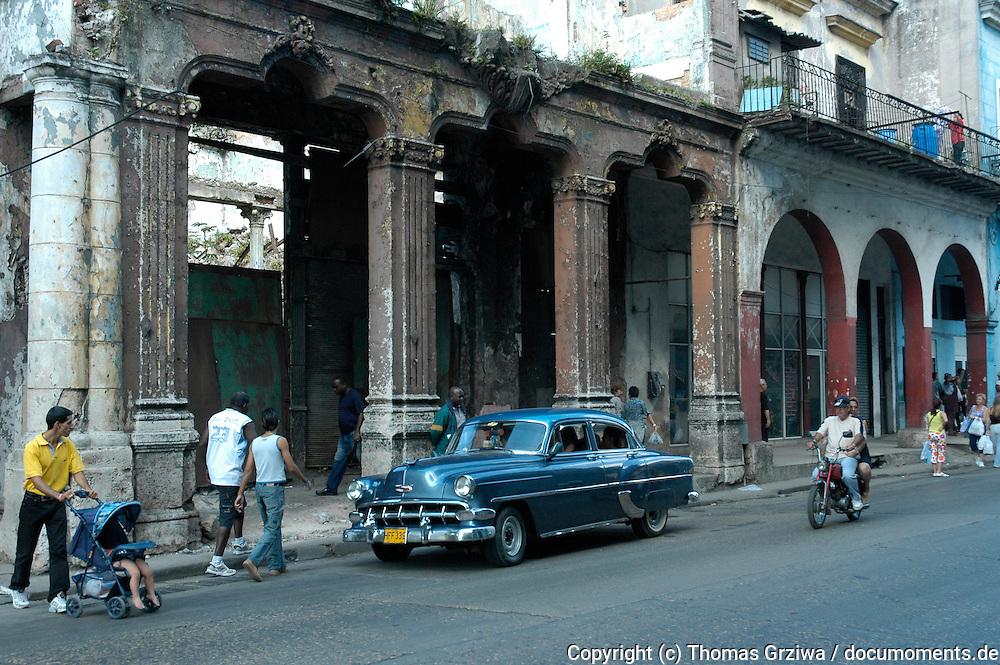 Straßenszene mit blauem Oldtimer und Kinderwagen vor verfallenem Prunkbau in der Altstadt von Havanna / Kuba.