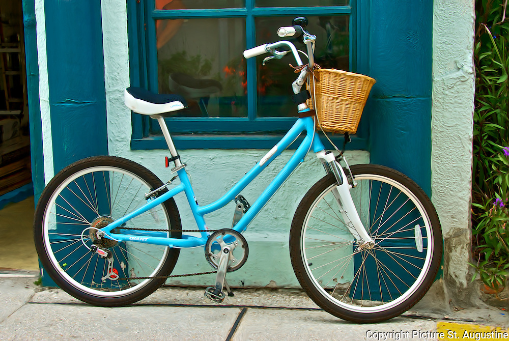 A blue bike with a wicker basket rest against a blue building on Aviles Street in downtown St. Augustine, Florida. Aviles Street is the oldest platted street in the United States.
