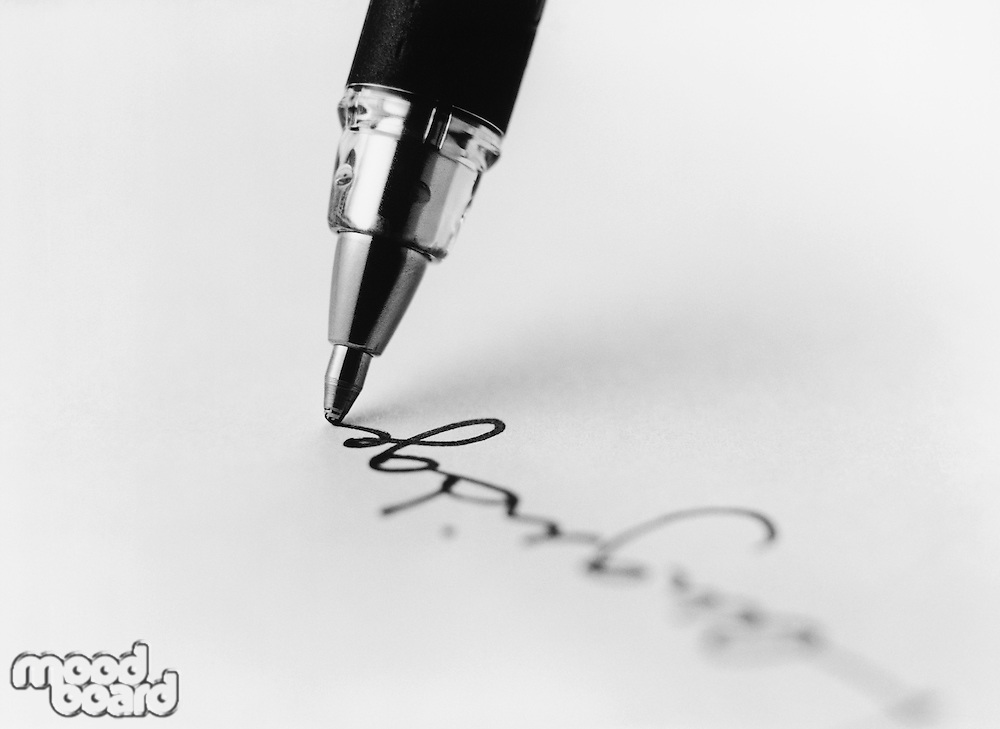 Tip of pen writing on paper (b&w) (close-up)
