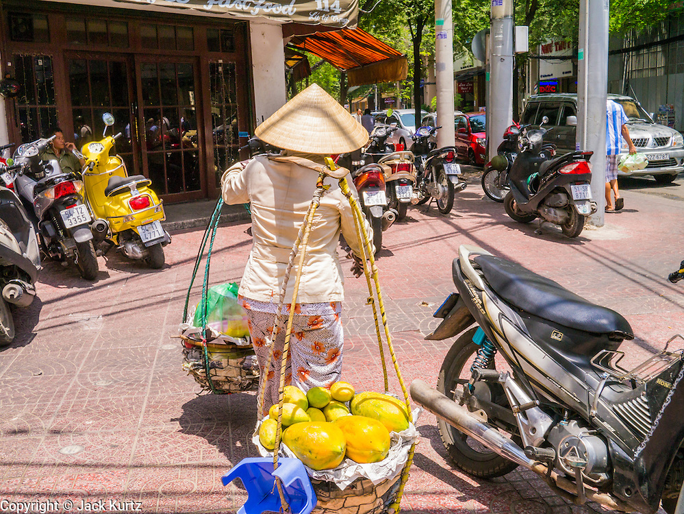 13 APRIL 2012 - HO CHI MINH CITY, VIETNAM: A Vietnamese woman carries fruit for sale through central Ho Chi Minh City, which used to be known as Saigon before the reunification with northern Vietnam in 1975. Ho Chi Minh City is the largest city in Vietnam and the commercial hub of southern Vietnam.      PHOTO BY JACK KURTZ
