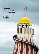 © Licensed to London News Pictures. 16/09/2012. Goodwood, UK . An air display passes a helter-skelter. People enjoy the atmosphere at the 2012 Goodwood Revival. The event recreates the glorious days of motor racing and participants are encouraged to dress in period dress. Photo credit : Stephen Simpson/LNP