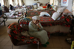 Warela Elia, 70, rests after lunch at a retirement home in Sadr City, Baghdad, Iraq, July 22, 2003. Even though most families in Iraq care for their aging relatives at home, there is still a need for the facility, which is the largest of its kind in Baghdad housing 45 women and 87 men. The facility was not looted during the war, but it is still lacks some funding and is in need of medications for patients with chronic conditions such as heart disease and diabetes.