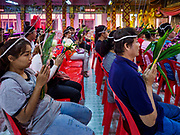 "30 DECEMBER 2017 - BANG KRUAI, NONTHABURI, THAILAND:  People pray during a resurrection ceremony at Wat Ta Khien, about 45 minutes from Bangkok in Nonthaburi province. The temple is famous for the ""floating market"" on the canal that runs past the temple and for the ""resurrection ceremonies"" conducted by monks at the temple. After the prayer, they lie in a coffin and ritualistically die before being reborn. Adherents believe it will improve their karma and help make up for past sins. PHOTO BY JACK KURTZ"